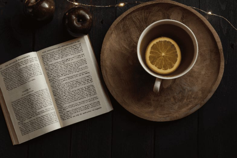 photo of cup of tea with book