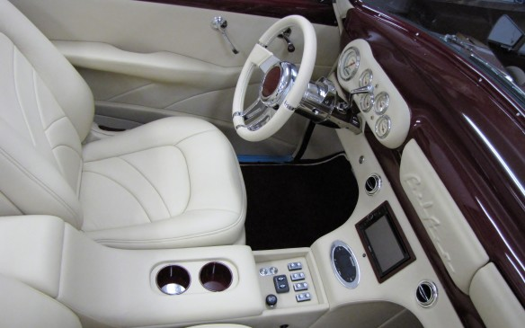 <p>The completed interior with custom seats, steering wheel, column-mounted shifter, instrument panel and console with navigation system.</p>