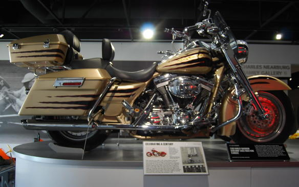 """<p>Opening its Custom Vehicle Operations (CVO) division in 1999, Harley-Davidson built a line of limited-edition, factory-custom motorcycles, which featured large-displacement engines and the """"Screamin' Eagle"""" branded performance upgrades.</p> <p>The CVO division later offered a Centennial Gold and Vivid Black paint scheme for the 100<sup>th</sup> anniversary of the Road King and Soft Tail CVO models.</p> <p>This 2003 Screamin' Eagle Road King, built on the framework of an FLHRI Road King, is powered by an air-cooled, twin-cam 103-cubic inch engine.</p>"""