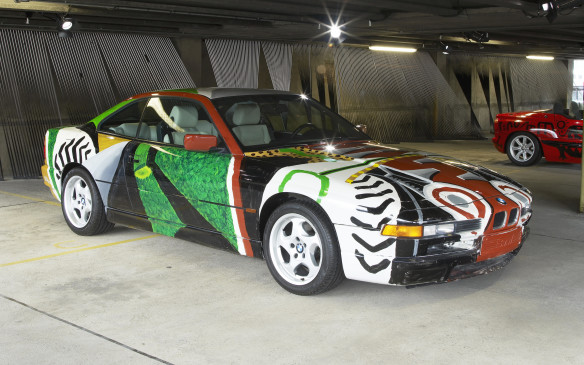 <p>The 14<sup>th</sup> BMW Art car was a 1995 BMW 850 CSi created by British-born, American pop artist David Hockney, whose aim was to portray the innermost depths of the car on the outside, albeit in fanciful stylized form. Recognizable elements a include a driver's image on the left door and a dog in the rear seat area.</p>