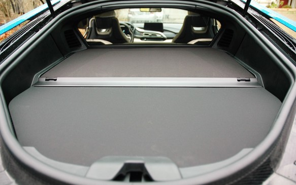 <p>Beneath the tailgate, the forward half of this panel covers the fully-enclosed engine housing, while the rear half lifts for access to the 154-L (5.4 cu.-ft.) trunk. Visibility to the rear is better than you might think, and a camera helps when backing up in confined spaces.</p>