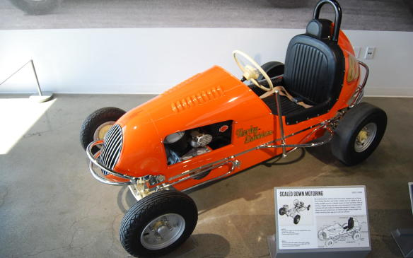 """<p>Measuring a mere six feet in length, standing only four inches off the ground, and reaching speeds of up to 60 miles per hour, the first midget car races were held in the early 1910's. However, it was not until the 1930's when the sport was officially recognized by a sanctioning body, leading to the construction of purpose-built tracks.</p> <p>Attractive to young drivers because of their comparatively low cost and the availability of do-it-yourself kits, three-quarter midgets were primarily """"one-offs"""" built in private garages and workshops using mix-and-match motorcycle parts, and remaining unique to their builders.</p> <p>Most midget racers were equipped with motorcycle engines and in-and-out gearboxes. This particular midget, however – powered by a 45-cubic inch Harley-Davidson flathead lacking such a gearbox – required a push start and would only stop when the brake was activated hard enough to stall the engine. It was recently restored from the ground-up.</p>"""