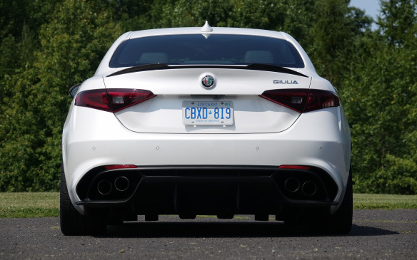 <p>This view of the Giulia Quadrifoglio, straight from the rear, shows its square-shouldered stance, wide tires and track, subtle carbon fibre spoiler and quadruple exhaust tips. The low shot also reveals the deep ribs of the fully-functional extractor that channels the air rushing underneath and spews it upwards, further improving both handling and stability at speed.</p>