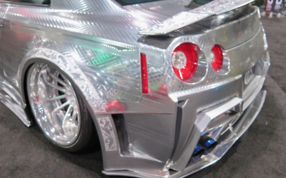 """<p>That's not chrome, it's paint! First unveiled at the Tokyo Motor Show last year, the Kuhl Racing GT-R's stunning metallic finish is dubbed """"3D Ultimate Engraving Metal Paint"""". Patterned with scales, crisscrosses, stripes, and even a floral design it is neither paint nor carving, but a bit of both called Artic 3D, a process where a material shaped to the curvature of the car's panels is """"engraved"""" by hand as it is pressed on the car much like fancy business cards with embossed print, on a much smaller scale.</p>"""