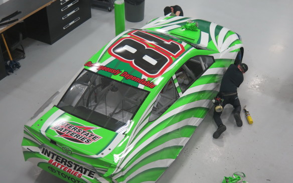 "<p>Here a technician is applying the ""wrap"" to the #18 Cup car. It is becoming more common for teams to change the appearance of the cars at various times during the year, for reasons related to sponsorship and/or special events. Using these giant wraps saves time and improves aerodynamics compared to painting the car, applying decals and then applying a clear coat of paint over the top.</p>"