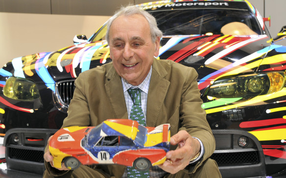 <p>Hervé Poulain, Godfather of the BMW Art Car Collection posed in front of the 17th BMW Art Car, holding a miniature of the first BMW Art Car by Alexander Calder in his hands.</p>