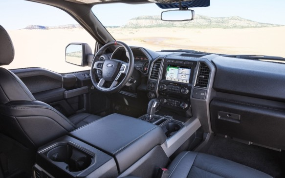 <p>In typical full-size pickup fashion, the Raptor's cabin is exceptionally spacious and practical, with this vast, treasure chest-like centre console and the requisite, Big Gulp-friendly cupholders. Grey-and-charcoal trim is subdued and purposeful, bordering on dull. Look for the optional colour accent packages. The instrument panel's centre stack, with its 8-inch touch screen, is exclusive to the Raptor in the F-150 family. It has various gauges, a trip computer, fuel economy data and setup menus for the towing and off-road applications.</p>
