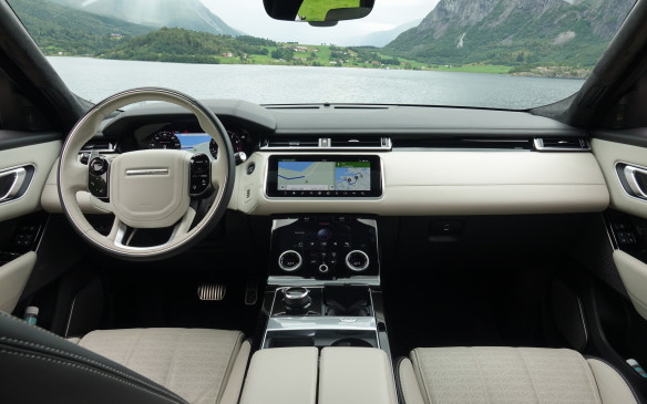 <p>The Velar's all-new instrument panel and centre console, angled forward noticeably, add a great sense of airiness and light in the cabin. More so with an abundance of ivory-coloured leather on the horizontal beam, door panels, centre armrest and two-tone steering wheel. Space and elbow room are more than generous in front, with comfy, well-sculpted and easily-adjusted seats. The driving position is impeccable, including a nice, flat footrest, and three different settings can be memorized with buttons on the driver's door. Visibility is great except for a large, high-mounted left outside mirror that blocks the view on the apex.</p>