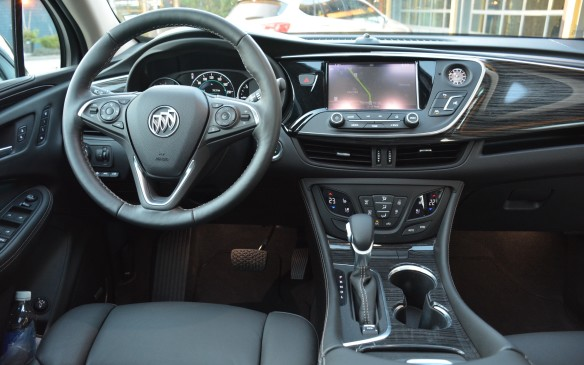 <p>Buick achieves a clean look throughout the Envision's cockpit without a lot of fuss. The eight-inch Intellilink infotainment unit stands out front and centre, but there's nothing much else to see. The instrument panel is simply laid out with a faux wood touch throughout to complement the soft leather.</p>