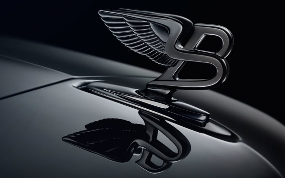 <p>F. Gordon Crosby also created the famed Bentley logo, which first adorned a 1930 8 Litre model as an option. Although it seems like a fairly simplistic design, it's asymmetrical to discourage forgeries. It was also one of the first hood ornaments to be banned in some countries because of its fixed base. The company did develop a retraction mechanism for pedestrian protection, but Bentleys with them were still recalled in 2010 over safety concerns, and now the company just uses a flat hood winged badge above the grille.</p> <p> </p>