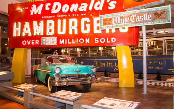 <p>Reinforcing the connection between the car and American society, many of the vehicles are displayed alongside iconic American symbols, like this 1956 Chevrolet Bel Air convertible beneath McDonald's Golden Arches.</p>