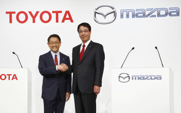 Toyota Motor Corp. President Akio Toyoda, left, and Mazda Motor Corp. President Masamichi Kogai pose for photographers prior to a press conference in Tokyo in May 2015.