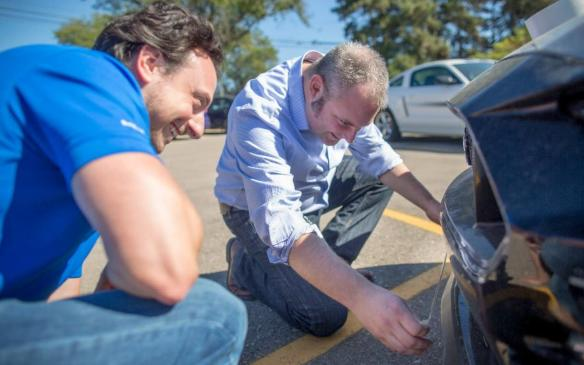 Ford engineer Mike Del Zio watches as Jonathan Gesek applies duct tape to Mustang lower grille to improve response.