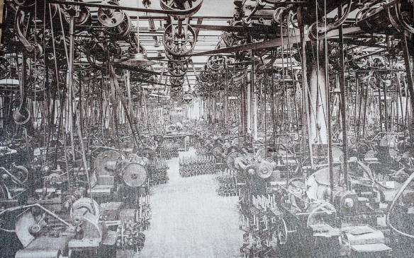 <p>This photo, one of many hanging on the walls of the museum, illustrates the organized chaos of plant life in those early days, with multitudes of machinery being driven by pulleys and belts from common overhead shafts.</p>