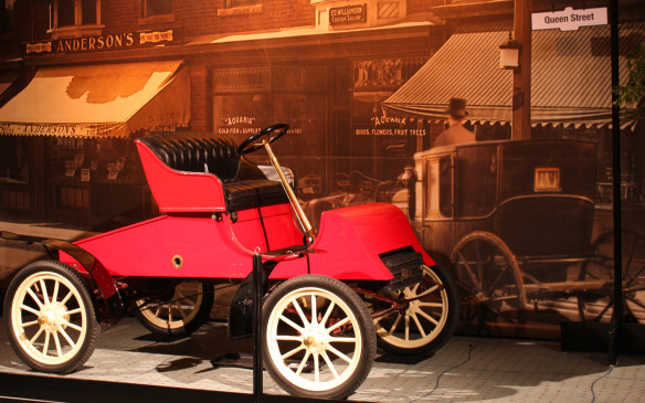 <p>If you're a fan of Murdoch Mysteries, you may recognize some of the backdrops in the Art and the Automobile display from the TV show. Several of the images were provided by the show's producer, Shaftesbury, and this 1903 Ford also appeared in the series. By the time the Ford Motor Company was established in 1903, automobile design had progressed from just buggies with engines to purpose-built vehicles, but not much further. Function still overruled form as this example, clearly attests.</p> <p></p>