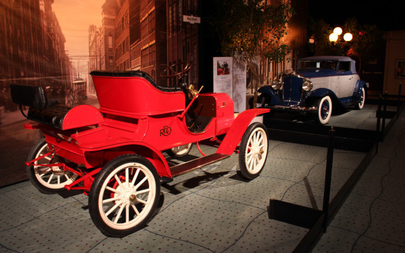<p>By 1908, the automobile had taken the form that most successors would follow for much of the next century, with an engine up front driving the rear wheels. Function ruled, but elements of style began to appear in the details, such as the wood trim and leather upholstery inthis Reo, which was 'owned' by George Crabtree and driven by 'Dr. Grace in theMurdoch Mysteries episode, Murdoch takes Manhattan'. In the background is a 1932Packard 900 'Shovel Nose' roadster</p>