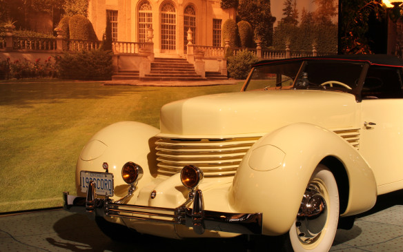 <p>Most of the cars within the gallery are displayed against a period-matching backdrop of Toronto-area architecture. The exhibit was designed and staged by event manager and CIAS media director, Beth Rhind, who is also an enthusiast of Toronto architecture and history. The mansion behind this 1936 Cord 810 Phaeton is Parkwood Estate in Oshawa, the former home of R.S. 'Sam' McLaughlin, the founder of General Motors of Canada. Arguably among the most beautiful cars ever produced, the Cord 810 was years ahead of its time in both design and engineering, if not reliability. Designed by Gordon Buehrig, originally for Duesenberg, its pontoon fenders, hidden headlamps, lack of running boards and clean surfaces established a new design paradigm.</p>