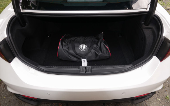 <p>Trunk space is decent, not exceptional, in all Alfa Romeo's new Giulia sedans. If the trunk itself is neither high, nor wide, the opening is both, ironically. While other Giulia models come with a handy 60/40 split-folding rear seatback, the Quadrifoglio's is fixed, most likely in the name of body rigidity. And the hot-rod Alfa Romeo is exceptional in this respect, which benefits both its handling and ride quality greatly. Our Quadrifoglio came with a luggage net and some solid chrome anchors, a $150 option, plus this nylon bag with a full, custom-fit car cover.</p>