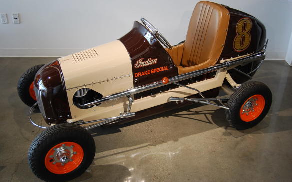 """<p>Like go-karting, midget racing was an introduction into the world of auto racing. By powering midgets with motorcycle engines, such as those from Indian or Harley-Davidson, midget builders had an available source of reliable power for their machines.</p> <p>By 1930, Drake Engineering began producing midget racing engines based on the Harley-Davidson """"Knucklehead."""" Best suited for short tracks, the engines housed a cooling system that lacked a water pump and tended to overheat. Company owner, Dale Drake installed an Indian engine in this three-quarter midget, deviating from the norm with a clutch-less in-and-out gearbox, making it necessary to push-start this midget.</p>"""