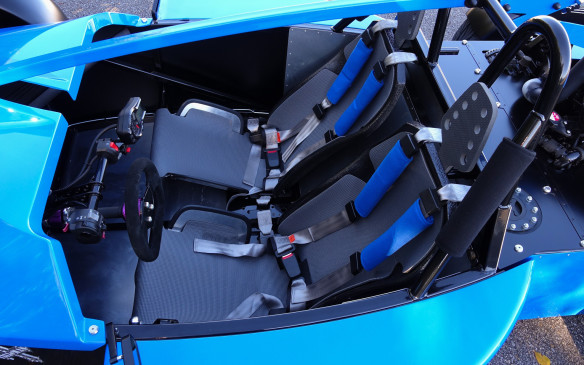 <p>The Talisman's driving quarters are as spare and purposeful as you can expect in a pure track machine that weighs only 545 kg(1 200 lb). The seats are built on fixed fibreglass shells with aluminium wings you can adjust to optimize thigh support. The seating surface is a close-cut, textured neoprene that keeps you in place resolutely, with the help of four-point harnesses. No wimpy cushioning here and none needed, since ride quality is quite good, with ample suspension travel and well-sorted damping. The soft sheaths on the top part of the belts encourage you to cinch them tightly.</p>