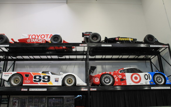 <p>There are more race cars in the collection, but not enough space to display them on the floor, so they're stacked on racks.</p>
