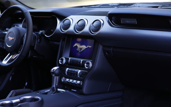 "<p>Inside the cabin, much of the chrome ""brightwork"" around the dials and on the door controls is now replaced by ""satin aluminum"" trim, for a classier look. Not all, but most. The Mustang badge above the glove box is now embossed, not stamped, and took a long time to get just right.</p>"