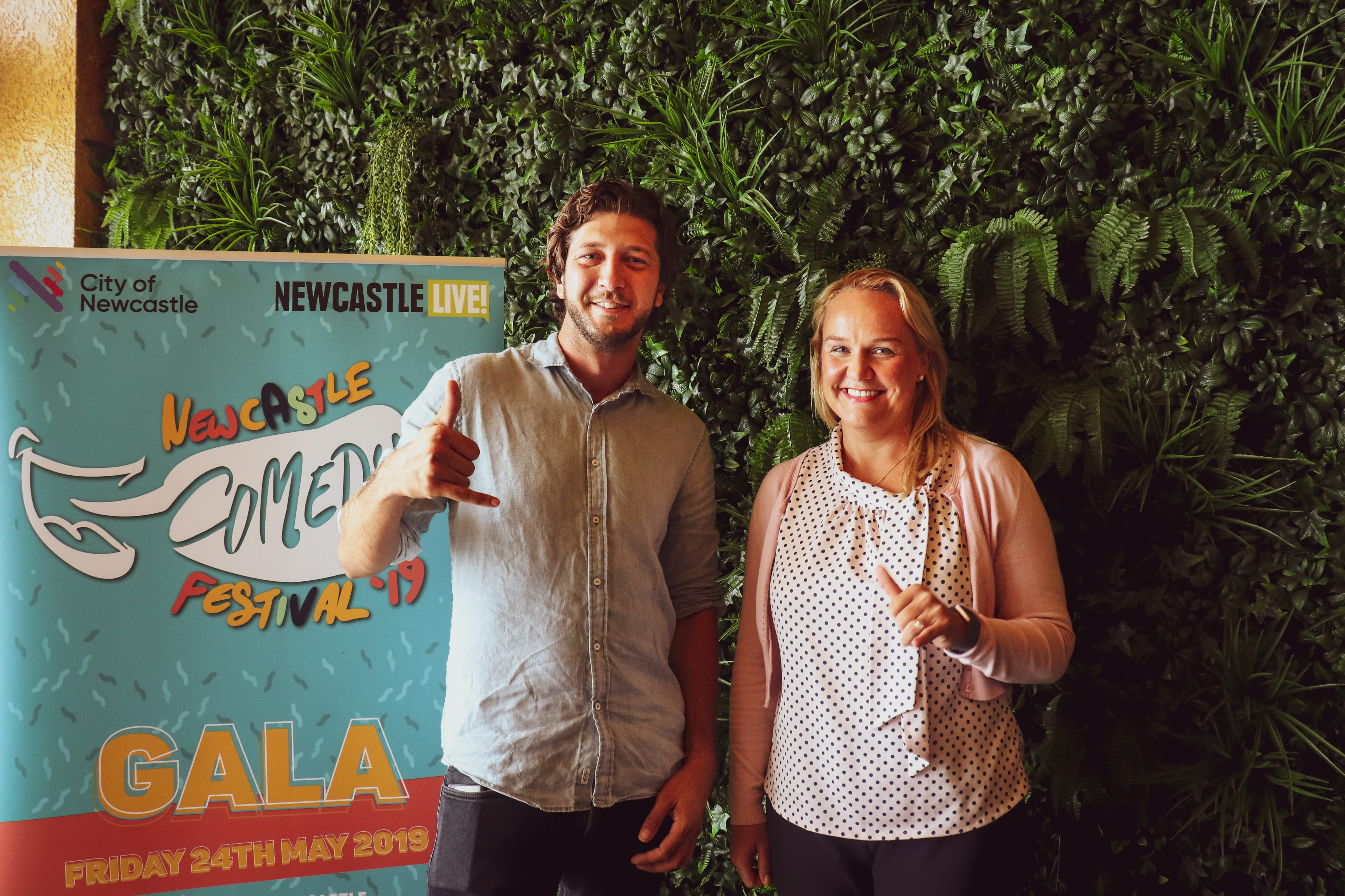 comedians andrew milos in front of newcastle comedy festival 2019 sign