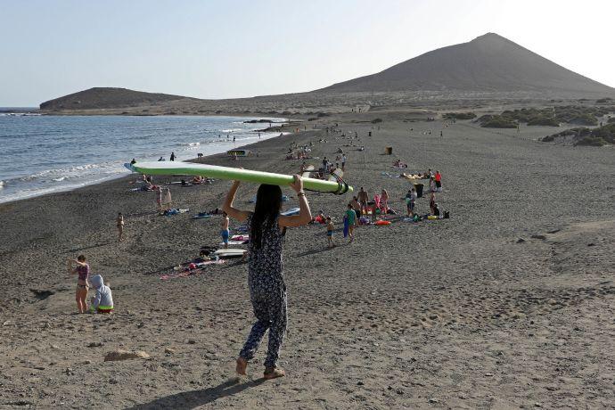 Eine Mädchen läuft mit SUP-Brett zum Wasser am Strand von El Médano