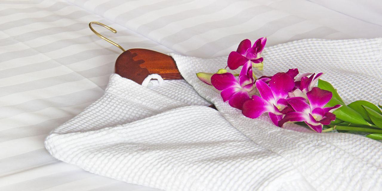 Weißer Bademantel auf dem Bett