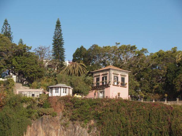 Ein rosa gestrichenes Haus auf einem Hügel über der Küste von Madeira