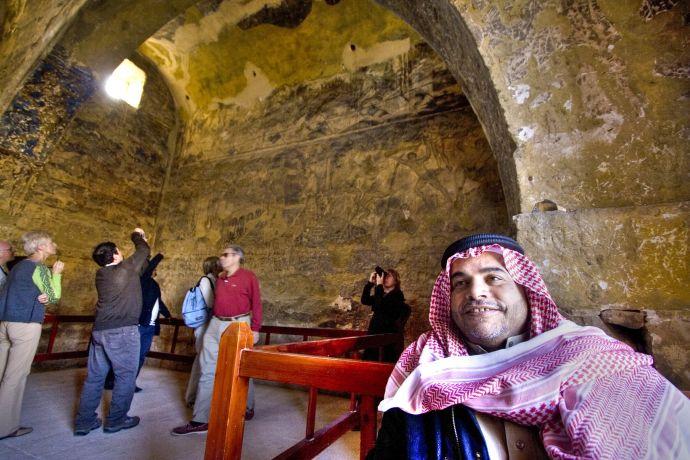 Beduinenführer und fotografierende Touristen im Wüstenschloss