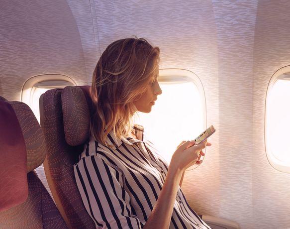 Frau mit Handy im Flugzeug