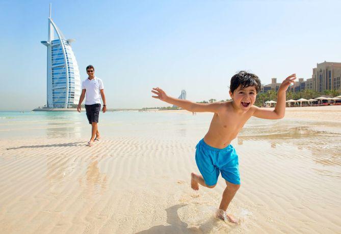 Familienurlaub in Dubai: ein Junge tollt über den weiten Sandstrand © visitDubai