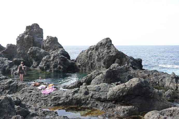 Badende in einem kleinen Felsenpool unweit der Playa de la Arena