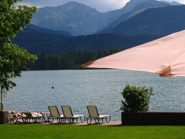 Blick auf den Wolfgangsee mit Sonnenschirm und Sonnenliegen