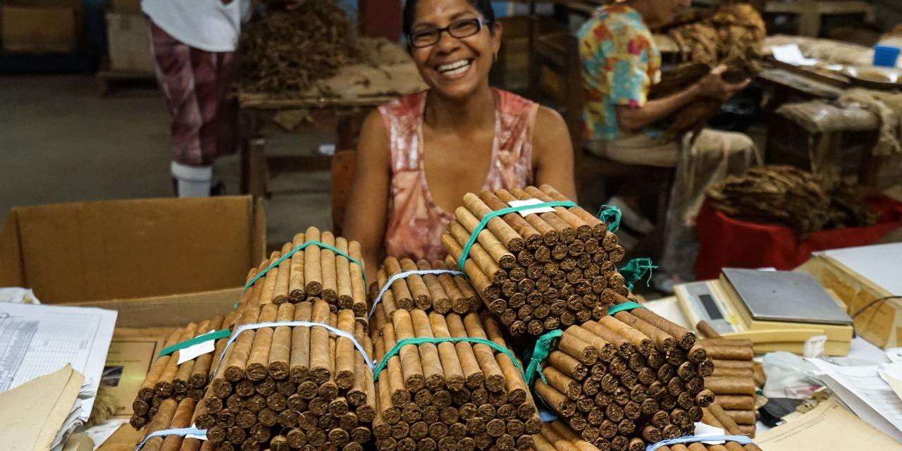 Eine lachende Mitarbeiterin in einer Zigarrenfabrik in Trinidad vor einem großen Stapel fertiger Zigarren