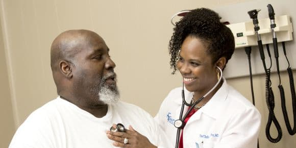 A female doctor smiles at her male patient while she's listening to his chest with a stethoscope.
