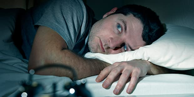 man in bed struggling to fall asleep