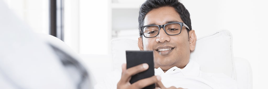 happy looking man with glasses looking at his smart phone