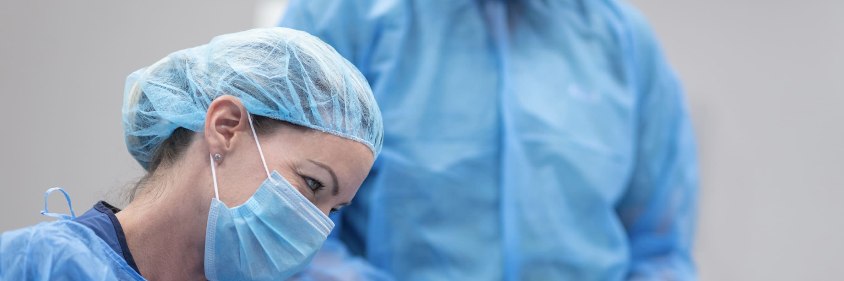 woman in surgical mask, gown and gloves holds patient's hand