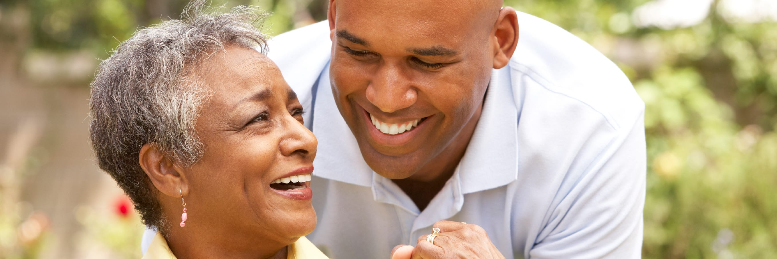 A man smiling over his mom's shoulder and holding her hand