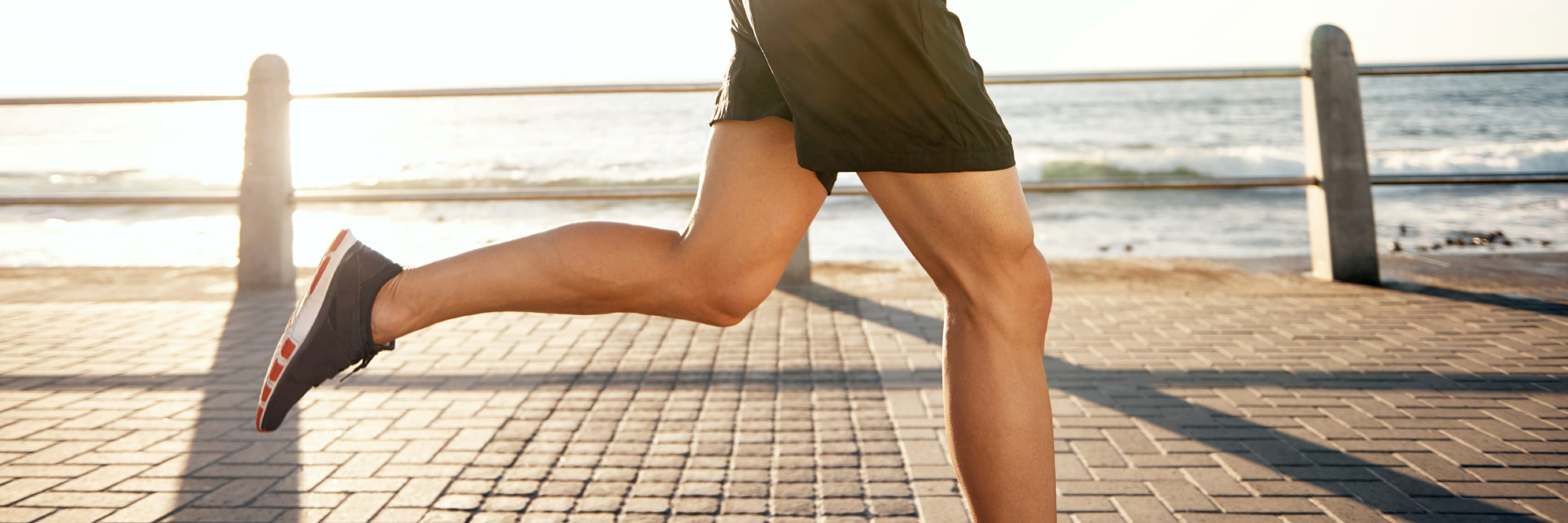 Close up of a man's legs as he runs on a paved walkway in front of water
