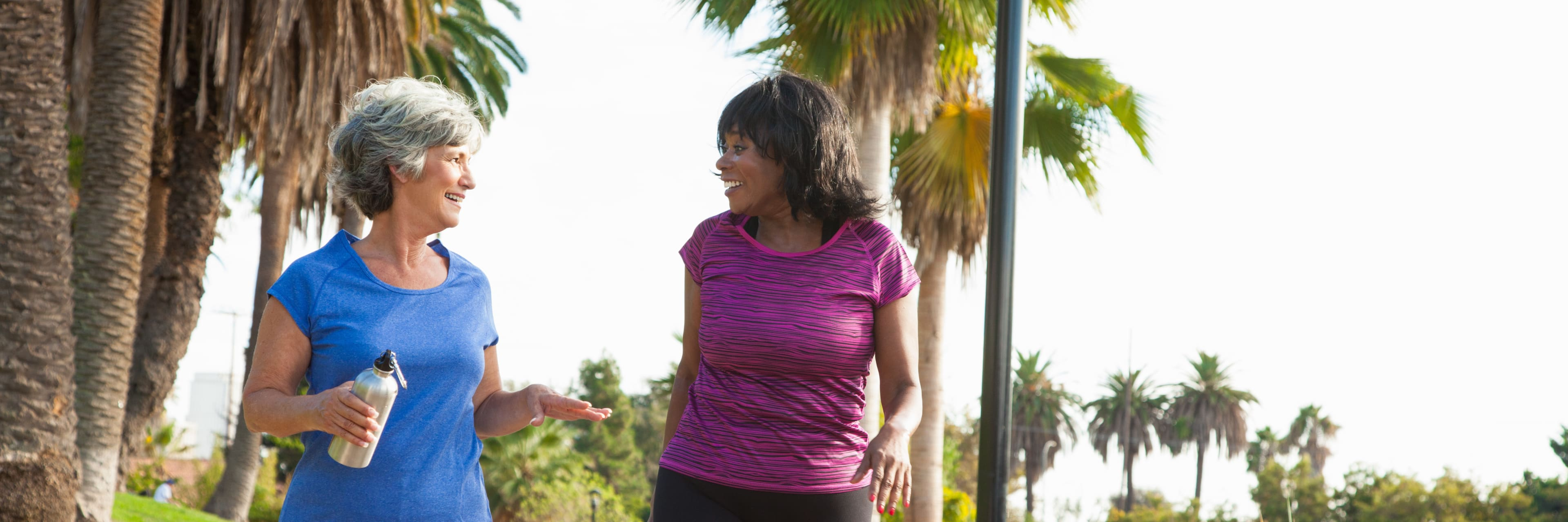 two women walking outside for exercise looking happy and energetic