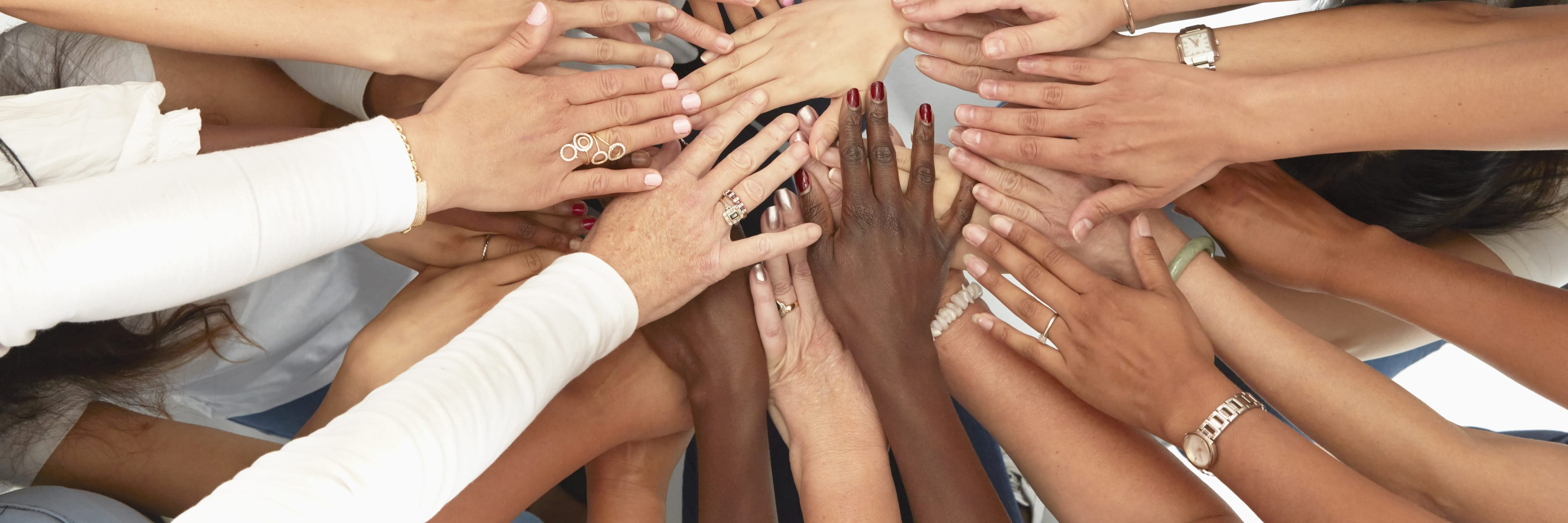 many different colored hands all on top of each other in a circle
