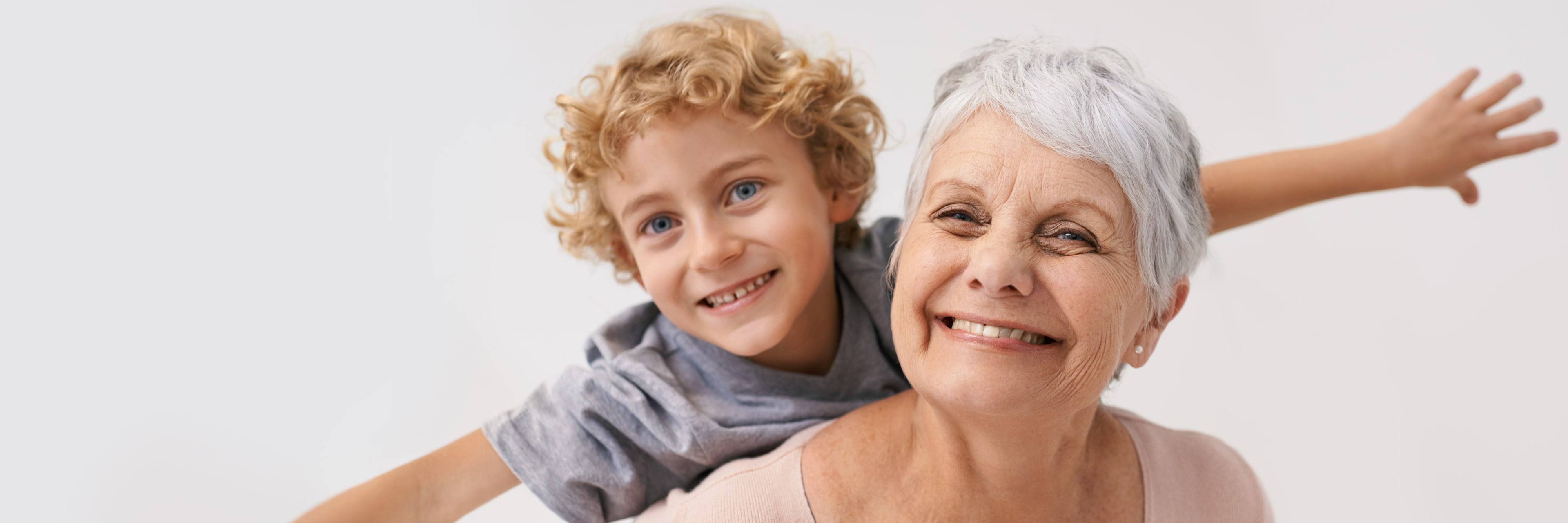 smiling woman giving her grandson a piggyback ride