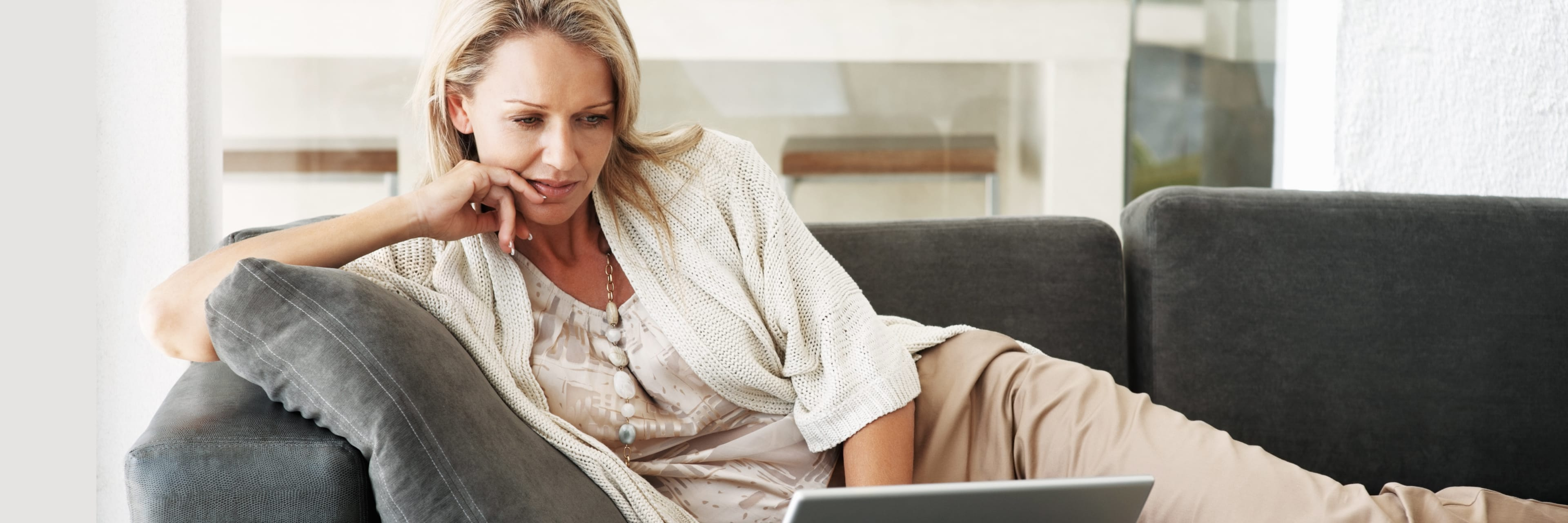 woman relaxing on couch looking at her laptop