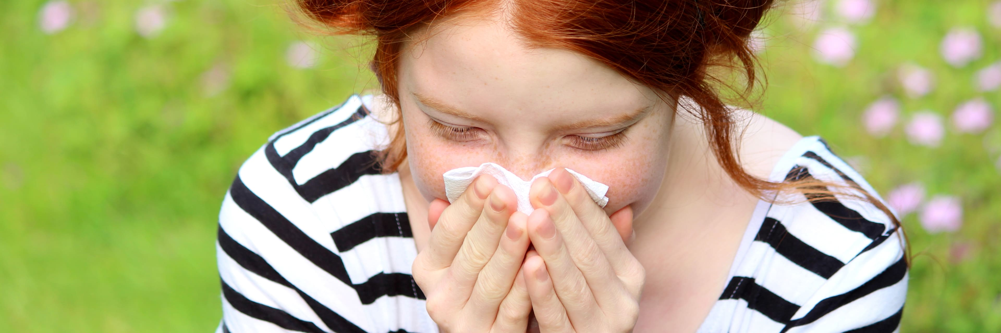 girl blowing her nose in a field