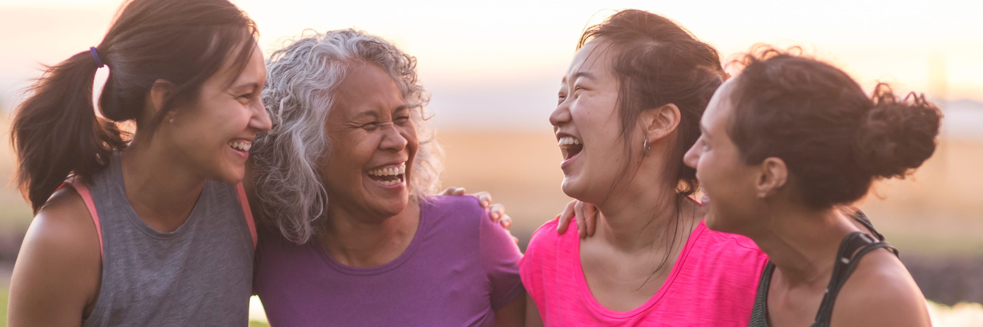 group of four women laughing together