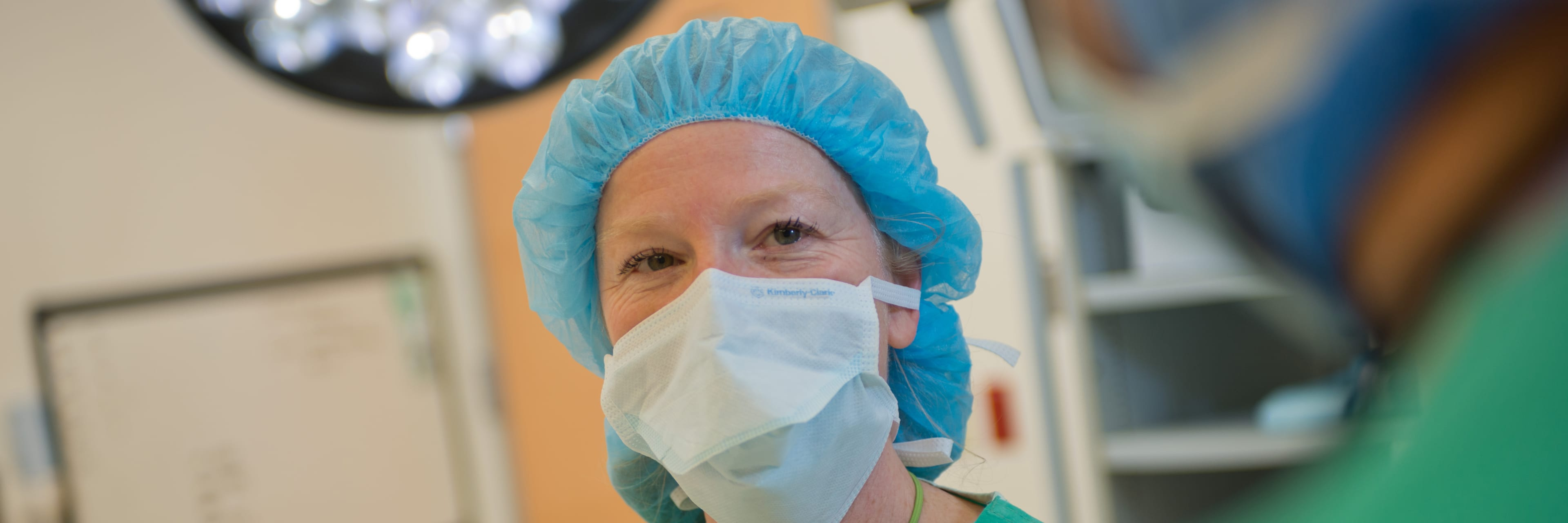 smiling female health care worker preparing for surgery