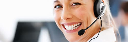 woman wearing a telephone operator headset smiling at you